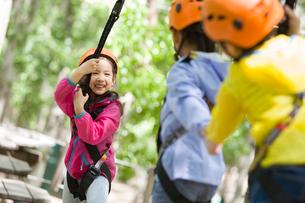 Happy children playing in tree top adventure parkの写真素材 [FYI02228109]