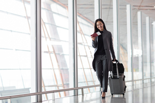 Businesswoman pulling wheeled luggage in airport lobbyの写真素材 [FYI02228132]