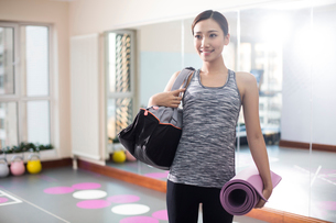 Young woman with yoga mat at gymの写真素材 [FYI02228171]