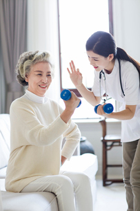 Senior woman exercising with dumbbell in nursing homeの写真素材 [FYI02228183]