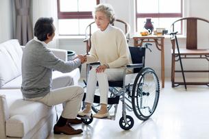 Senior man taking care of wife in wheel chairの写真素材 [FYI02228204]