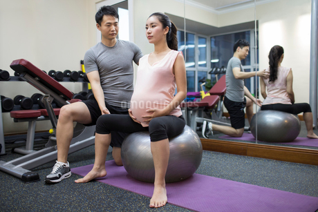 Pregnant woman working with trainer at gymの写真素材 [FYI02228218]