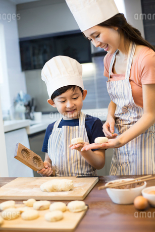 Happy young mother and son baking togetherの写真素材 [FYI02228244]