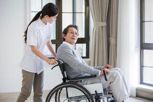 Nursing assistant taking care of senior man in wheel chairの写真素材 [FYI02228260]