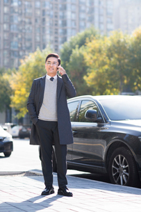 Confident Chinese businessman talking on the phoneの写真素材 [FYI02228278]