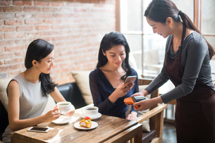 Chinese friends paying with smart phone in cafeの写真素材 [FYI02228285]