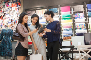 Chinese friends paying with smart phone in clothing storeの写真素材 [FYI02228301]