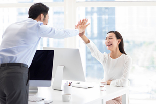 Confident Chinese business people high fiving in officeの写真素材 [FYI02228344]