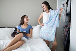 Young woman choosing dress from wardrobeの写真素材 [FYI02228405]