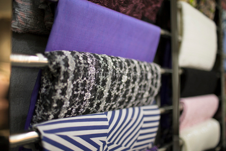 Different fabric swatches hanging on a designer's material rackの写真素材 [FYI02228419]