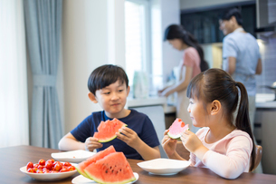 Happy siblings eating watermelonの写真素材 [FYI02228426]