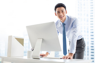 Young Chinese businessman using computer in officeの写真素材 [FYI02228435]