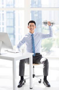 Young Chinese businessman exercising in officeの写真素材 [FYI02228440]