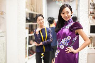Chinese fashion designer examining dress on customerの写真素材 [FYI02228454]