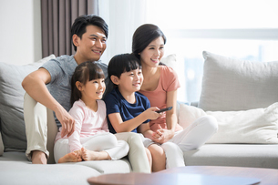 Happy young family watching TVの写真素材 [FYI02228468]