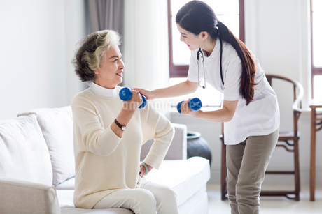Senior woman exercising with dumbbell in nursing homeの写真素材 [FYI02228478]