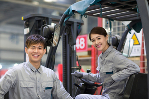 Confident workers driving forklift in the factoryの写真素材 [FYI02228502]