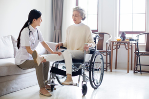 Nursing assistant taking care of senior woman in wheel chairの写真素材 [FYI02228520]