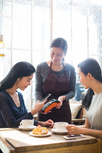 Chinese friends paying with smart phone in cafeの写真素材 [FYI02228521]
