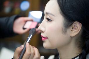 Makeup artist applying make-up to young womanの写真素材 [FYI02228527]