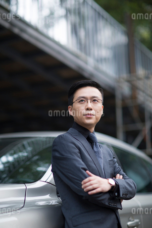 Mid adult businessman standing next to the carの写真素材 [FYI02228537]