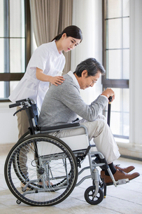 Nursing assistant taking care of senior man in wheel chairの写真素材 [FYI02228546]