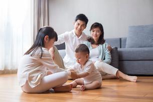 Happy young family sitting on wooden floorの写真素材 [FYI02228554]