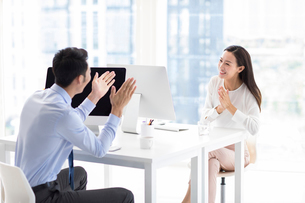 Confident Chinese business people talking in officeの写真素材 [FYI02228565]