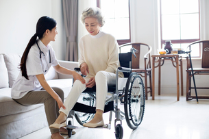 Nursing assistant taking care of senior woman in wheel chairの写真素材 [FYI02228578]