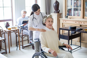 Nursing assistant taking care of senior woman in wheel chairの写真素材 [FYI02228581]