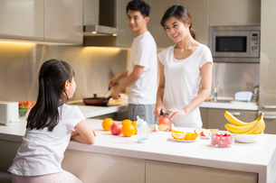 Happy young family cooking in kitchenの写真素材 [FYI02228605]