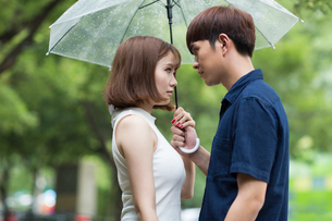 Young couple holding umbrellaの写真素材 [FYI02228607]
