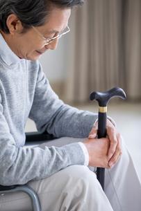 Senior man in wheelchair holding a caneの写真素材 [FYI02228624]