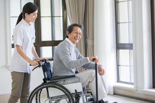 Nursing assistant taking care of senior man in wheel chairの写真素材 [FYI02228653]