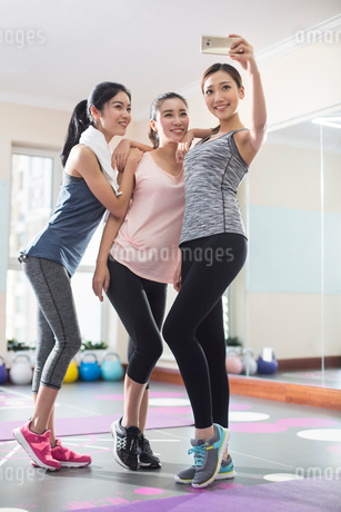 Young women taking self portrait at gymの写真素材 [FYI02228671]