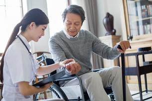 Nursing assistant taking care of senior man in wheel chairの写真素材 [FYI02228713]