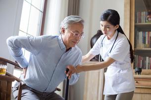 Nursing assistant taking care of senior manの写真素材 [FYI02228735]