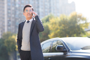 Confident Chinese businessman talking on the phoneの写真素材 [FYI02228744]
