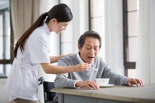 Nursing assistant taking care of senior man in wheel chairの写真素材 [FYI02228751]