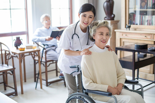 Nursing assistant taking care of senior woman in wheel chairの写真素材 [FYI02228782]