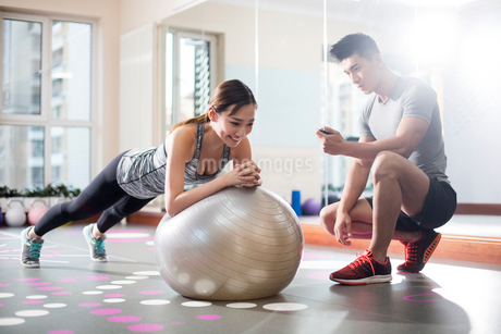 Young woman working with trainer at gymの写真素材 [FYI02228872]