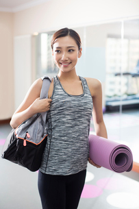 Young woman with yoga mat at gymの写真素材 [FYI02228911]