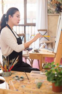 Female artist painting in studioの写真素材 [FYI02228929]