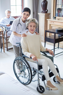 Nursing assistant taking care of senior woman in wheel chairの写真素材 [FYI02228932]