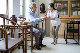 Nursing assistant taking care of senior manの写真素材 [FYI02228941]