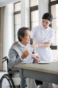 Nursing assistant taking care of senior man in wheel chairの写真素材 [FYI02228954]