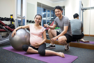 Pregnant woman working with trainer at gymの写真素材 [FYI02228975]