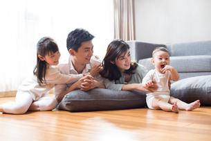 Happy young family lying on wooden floorの写真素材 [FYI02228984]