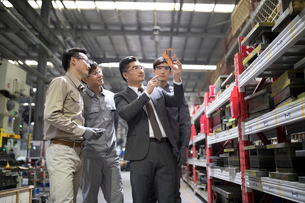 Businessman and engineers checking machine parts in the factoryの写真素材 [FYI02228988]