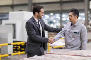 Businessman and engineer shaking hands in the factoryの写真素材 [FYI02228991]